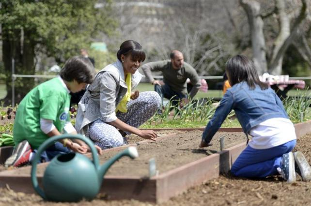 Michelle Obama en el huerto de la Casa Blanca plantando junto con algunos de los escolares estadounidenses invitados (Fuente: noticias.lainformacion.com)